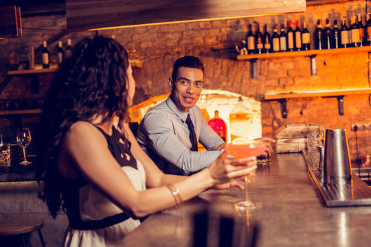 Curly woman drinking cocktail in bar talking to man