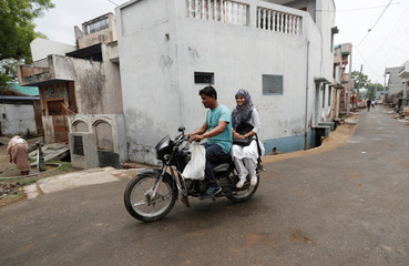 Sharfuddin, a cloth shop owner and his niece Aisha, a law student, ride a motorbike  in Nayabans