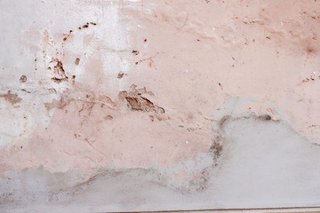 Old weathered painted wall background texture. White dirty peeled plaster wall with falling off...