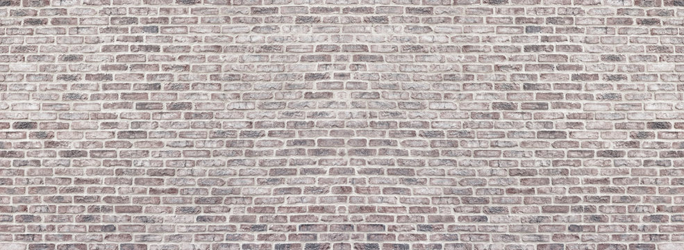 Wide light red shabby brick wall texture. Old masonry panorama. Whitewashed rough brickwork panoramic vintage background