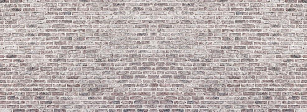 Wide light red shabby brick wall texture. Old masonry panorama. Whitewashed rough brickwork panoramic vintage background