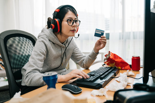 young lazy college girl nerd at home on summer break off from school holding credit card paying online e commerce buying game points. asian woman geek with headphones playing computer internet.
