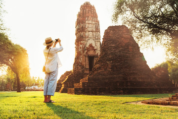 Woman traveler takes a photo of atcient Wat Chaiwatthanaram Buddhist temple in holy city Ayutthaya, Thailand