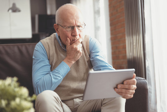 Confused senior man using a digital tablet