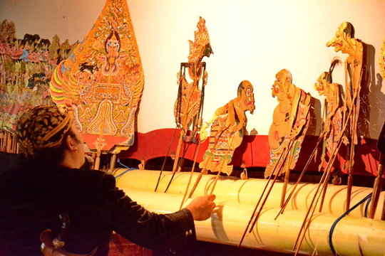 a puppeteer when playing a shadow puppet on a stage