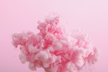 Wall Mural - Close up view of pink smoky paint in water isolated on pink