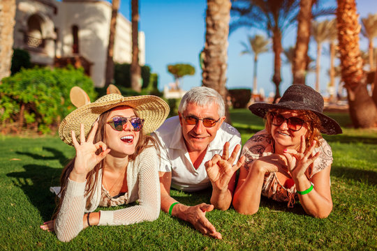 Senior couple lying on grass with adult daughter by hotel. Happy people enjoying vacation. Family values