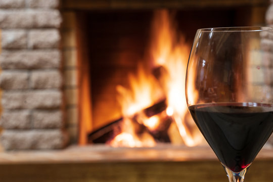 Glass of wine against cozy burning fireplace background, christmas evening.