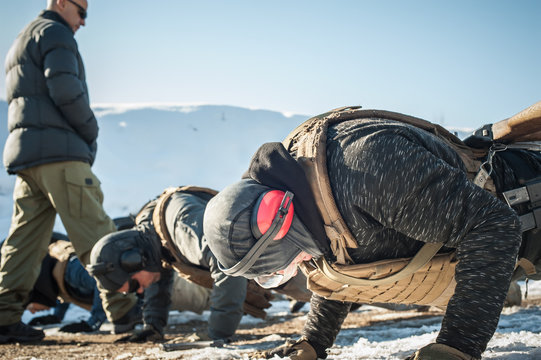 Instructor and army soldiers have hard training and doing push-ups