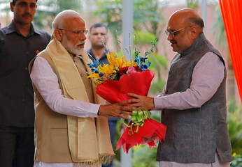 India's PM Modi receives a flower bouquet from BJP President Amit Shah upon his arrival to attend a thanksgiving ceremony by BJP leaders to its allies at the party headquarters in New Delhi