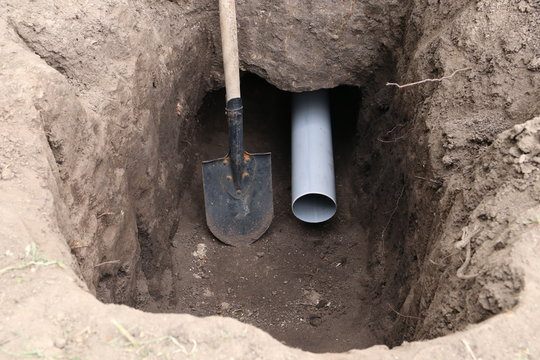 Deep pit and tunnel under the foundation of the house. Sewer pipe in a tunnel