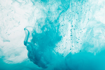 Close up view of blue paint swirls in water