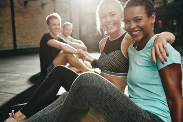 Two smiling women sitting in a gym after working out Wall mural
