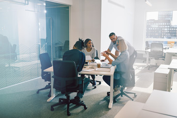 Work colleagues discussing business together during an office me