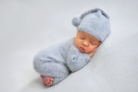 Sleeping newborn boy in the first days of life on white background