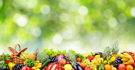 Fruits, vegetables, berries on green natural blurred background. Wall mural