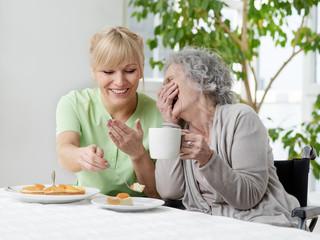 Seniorin und Pflegerin haben Spass beim Kaffee