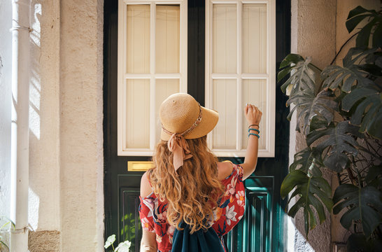 Woman in a hat wearing generic red dress is knocking the door