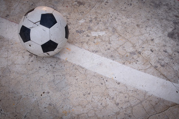 Old ruined damaged soccer ball put on cracked cement field