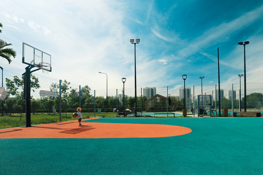 Little boy playing basketball outside in summer