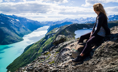 Young, hiking woman looks  into the Jotunheimen mountains.  Norway