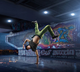 Male Hip Hop Dancer. Beautiful man dancing at night on the background of graffiti wall