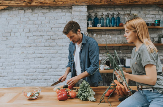 Lovely cheerful young couple cooking dinner together