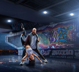 Hip Hop Dancers. Beautiful couple dancing at night on the background of graffiti wall