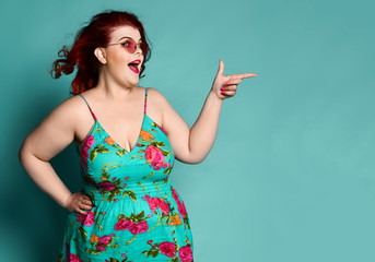 Joyful Overweight redhead lady plus-size woman in sunglasses shows a gesture sign finger - gun, point at free text space on mint