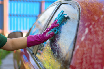 Woman in rubber gloves washes a red car. Cleaning detergent.