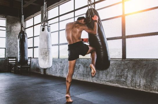 Muay thai fighter training in gym with punching bag