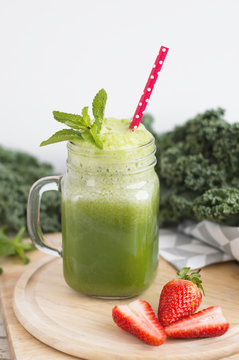 Green kale smoothie served with mint and strawberry. Healthy drink. Detox concept