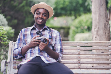 African Man Traveler holding camera with green natural background
