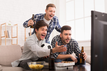 Soccer Fans Emotionally Watching Game In Living Room