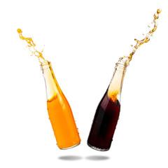 Cola and orange soda splashing out of glass bottle isolated on white background.