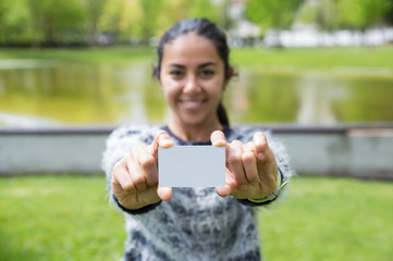 Smiling young woman showing blank plastic card in city park. Blurred pretty lady wearing sweater and standing with blurred green view in background. Introduction concept. Front view.