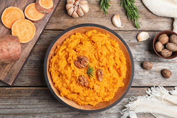 Flat lay composition with mashed sweet potatoes on wooden background