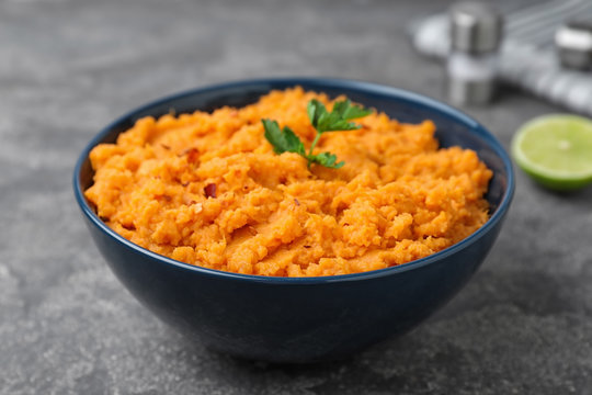Bowl with mashed sweet potatoes on grey table