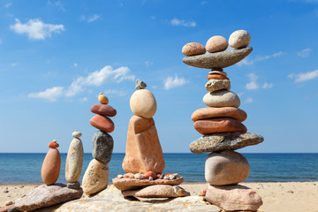 Photo sur Plexiglas Zen pierres a sable Several Rock zen pyramids of colorful pebbles on a beach on the background of the sea. Concept of balance, harmony and meditation.