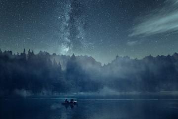 Nachtangeln auf einem See bei Nacht mit Sternenhimmel und Nebel. Im Hintergrund Wald, Berge und die Milchstraße