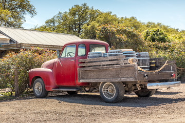 Red, old pickup truck and wine barrels
