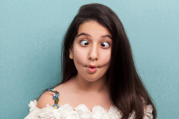 Portrait of funny beautiful brunette young girl with black long straight hair in white dress standing with crossed eyes, fish lips and crazy expression. indoor studio shot isolated on blue background.