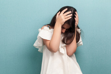Portrait of sad beautiful brunette young girl with black long straight hair in white dress standing holding her head down and depressed. indoor studio shot isolated on blue background.