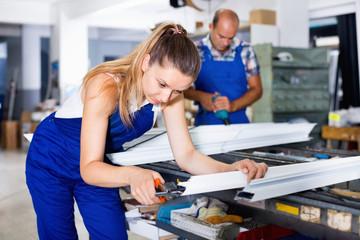 Female worker cutting metal-plastic profiles in workshop, using nippers