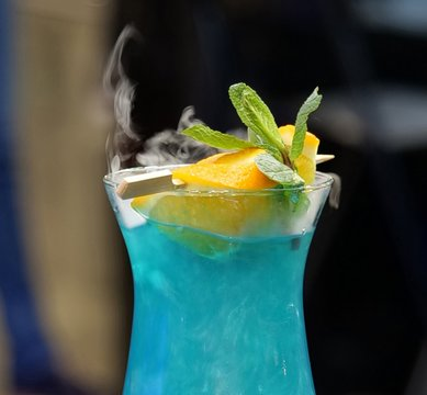 Cocktail blue lagoon with a slice of lemon and smoke
