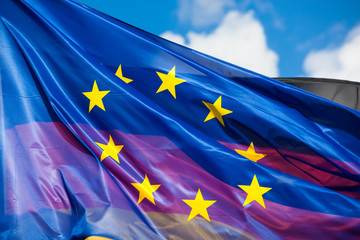 Waving Flag of the European Union in Foreground, Flag of Germany seen through