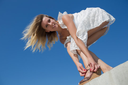Female person in white dress bends