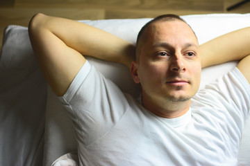 Picture showing young man stretching in bed. Cheerful young man is waking up after sleeping in the morning. He is yawing and stretching . He is lying in the bed.