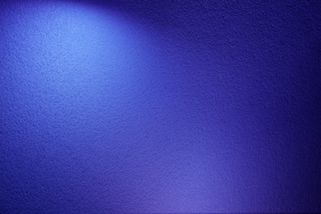 White and violet spot of light on blue textural background
