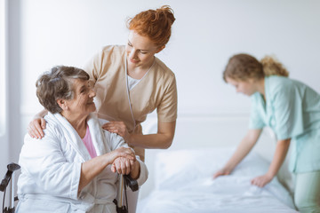 Elderly woman on wheelchair in nursing home with helpful doctor at her side and young nurse making the bed